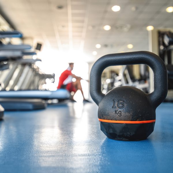 Close-Up of Kettlebell and Fitness Enthusiast in Background