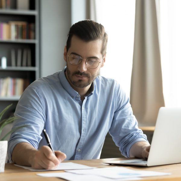 Concentrated,Young,Caucasian,Man,In,Glasses,Sit,At,Desk,Work